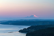View of Mount Rainier (14 409 ft / 4 392 meters), Whidbey Island, and Similk Bay at sunset.  Photographed from Mt. Erie Park(117 miles / 188 km away) in Anacortes, Washington, USA.