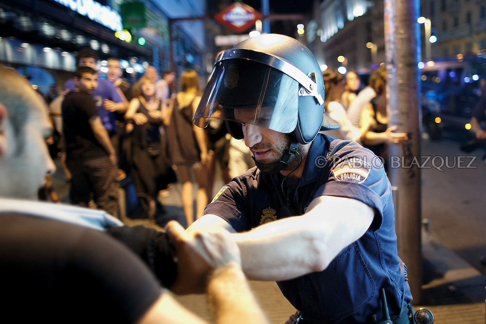 A riot policeman grabs a protestor at Gran Via during a demonstration against the Spanish government, on Thursday, July 18, 2013, in Madrid, Spain. Thousands demonstrators demanding the resignation of Prime Minister Mariano Rajoy and its party gathered in front of the People's Party headquarter. Rajoy rejected demands to resign after more alleged secret payments and test messages related to former political party treasurer Luis Barcenas under investigation appeared. The spectacle of alleged greed and corruption has enraged Spaniards hurting from austerity and sky high unemployment.