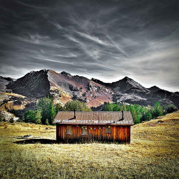 "Pioneer Cabin near Sun Valley Idaho with the Pioneer Mountain Range in the back ground. Taken at mid-day in the late fall,  Sign on roof reads: ""The higher you get, the higher you get""  This cabin was built by the Sun Valley Company as a back country ski hut."