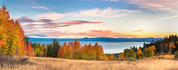 """""""Aspens Above Lake Tahoe 4"""" - Panoramic photograph of yellow, orange, red, and green fall colored aspens above a blue Lake Tahoe, taken at sunset."""
