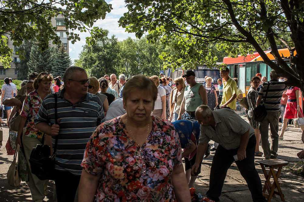 SVITLODARSK, UKRAINE - JULY 8, 2016: People pass through a small vegetable market on the sidewalk in Svitlodarsk, Ukraine. The village is located less than ten miles from the front lines with rebel-controlled territory. CREDIT: Brendan Hoffman for The New York Times