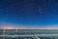 Orion and the Dog Stars (Procyon and Sirius), and Gemini above, rising over frozen Lake MacGregor in southern Alberta, on February 2, 2017, on a clear moonlit night, with a 6-day Moon lighting the scene. Note the glitter path reflection of Sirius in the ice. The Beehive star cluster, M44, is at far left, in Cancer. <br /> <br /> This is with the Sigma 20mm Art lens and Nikon D750.