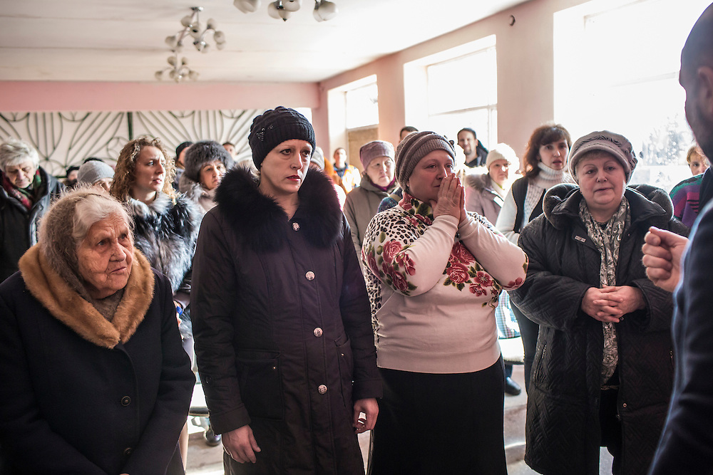 MARIINKA, UKRAINE - FEBRUARY 20, 2016:  Congregants at the Christian Help Center of the Church of the Transfiguration listen to a visiting pastor from Russia during a service in Mariinka, Ukraine. The Donetsk suburb has been the scene of some of the heaviest fighting recently between Ukrainian forces and pro-Russian rebels. CREDIT: Brendan Hoffman for The New York Times