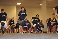Melissa Griffith (standing) and Jonathan Hickman participate in the wheelbarrow race during the Rebelthon fundraiser to benefit Le Bonheur Children's Hospital in Oxford, Miss. on Friday, April 5, 2013.