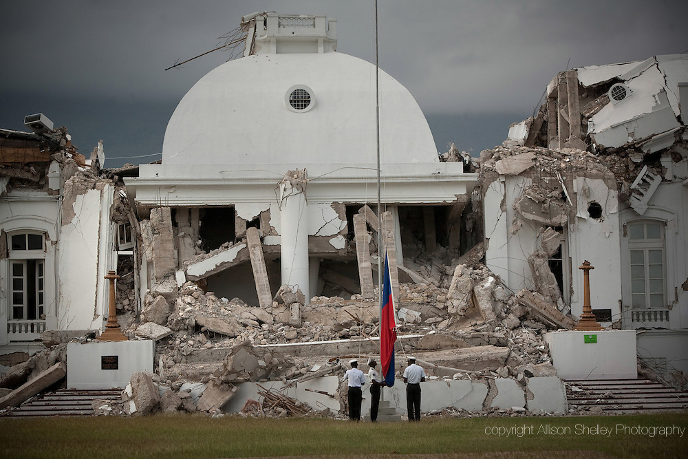 Officials raise the Haitian flag in front of the destroyed national palace in downtown Port-au-Prince, Haiti, before a band plays the national anthem the morning of Friday, February 26, 2010.  This ritual happens every morning. The palace was designed in 1912 by Haitian architect Georges H. Baussan.  U.S. Naval engineers supervised its completion in 1920.