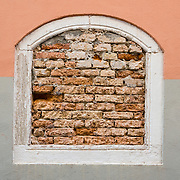 Brick filled window, Venice (Venezia), Italy, Europe. Venice (Venezia), founded in the 400s AD, is capital of Italy's Veneto region, named for the ancient Veneti people from the 900s BC. The romantic City of Canals stretches across 100+ small islands in the marshy Venetian Lagoon along the Adriatic Sea, between the mouths of the Po and Piave Rivers. The Republic of Venice was a major maritime power during the Middle Ages and Renaissance, a staging area for the Crusades, and a major center of art and commerce (silk, grain and spice trade) from the 1200s to 1600s. The wealthy legacy of Venice stands today in a rich architecture combining Gothic, Byzantine, and Arab styles. Venice and the Venetian Lagoon are honored on UNESCO's World Heritage List.