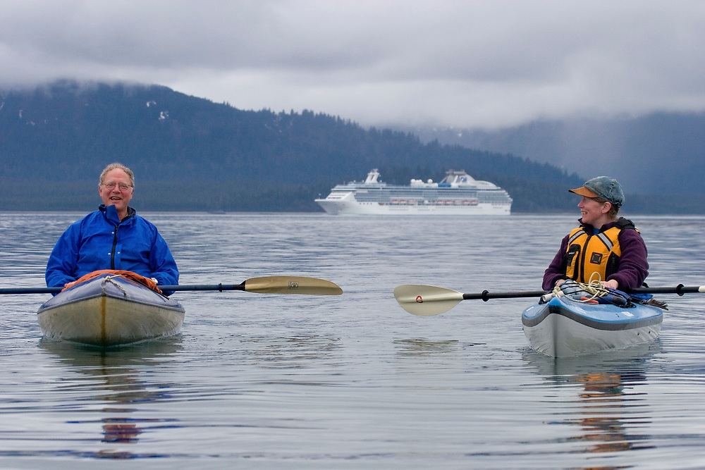 Two kayakers laugh with cruise ship behind them