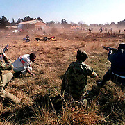 FUNERALS POLICE UNREST SOUTH AFRICA 20 JUN 1992: South African police fire on African National Congress  supporters when they tried to check the identity of a man shot dead by police in this Boipatong field earlier Saturday June 20, 1992. 45 ANC supporters, including women and children were massacred by Zulu supporters of the Inkatha Freedom Party the night before. (Photo by Greg Marinovich)