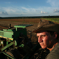 A worker sits on top of his harvesting machine while waiting for a truck to come pick up harvested soybeans just outside of Marcelândia, in Mato Grosso state, in Brazil on April 6, 2008. (Photo/Scott Dalton).