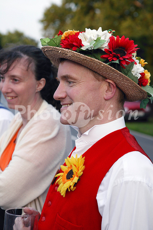 Morris dancer wearing costume standing outdoors smiling,