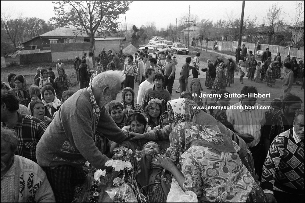 BADEA MIHAI KNEELS BESIDE THE BODY OF HIS WIFE, TALIA, AS THE CORTEGE MAKES ITS WAY FROM THE CAMP TO THE CHURCH. SINTESTI, ROMANIA. MAY 1997..©JEREMY SUTTON-HIBBERT 2000..TEL./FAX.+44-141-649-2912..TEL.  +44-7831-138817.