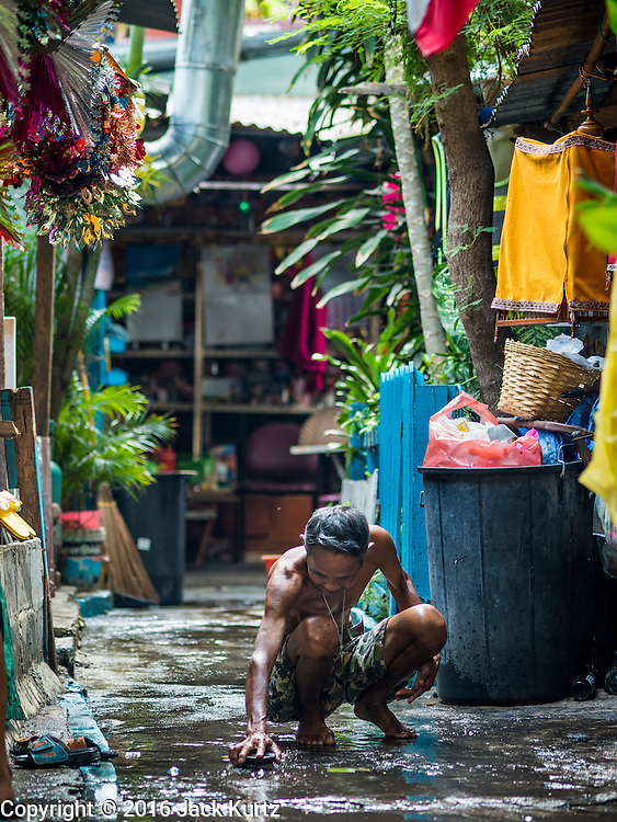 08 APRIL 2016 - BANGKOK, THAILAND:   A man scrubs the sidewalk in front of his home in Mahakan Fort. The community is known for fireworks, fighting cocks and bird cages. Mahakan Fort was built in 1783 during the reign of Siamese King Rama I. It was one of 14 fortresses designed to protect Bangkok from foreign invaders, and only of two remaining, the others have been torn down. A community developed in the fort when people started building houses and moving into it during the reign of King Rama V (1868-1910). The land was expropriated by Bangkok city government in 1992, but the people living in the fort refused to move. In 2004 courts ruled against the residents and said the city could take the land. The final eviction notices were posted last week and the residents given until April 30 to move out. After that their homes, some of which are nearly 200 years old, will be destroyed.   PHOTO BY JACK KURTZ