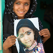 Girl from Rajasthan (Thar desert, India) holds a photo taken by the (same) photographer a few years earlier.