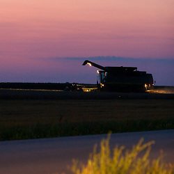 A big combine harvests a crop of summer wheat from a field in Illinois as the sun sets on this warm day.