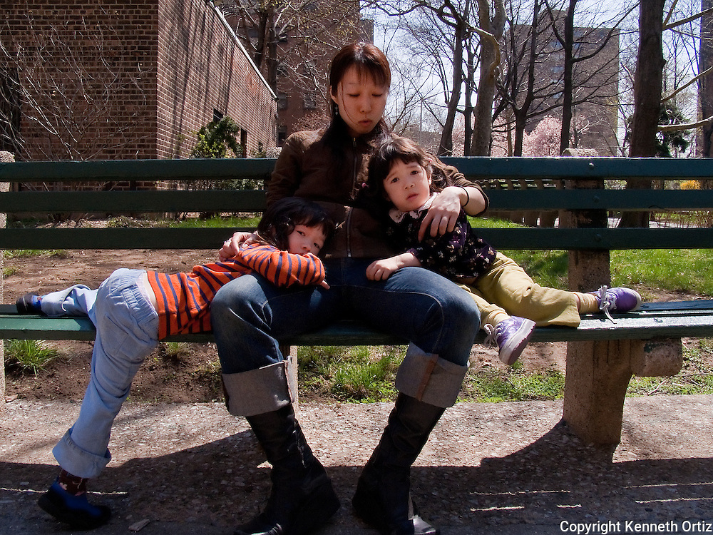 A mother with her two children sitting on a bench in the Queensview Gardens in Astoria Queens New York.