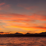 A fiery fall sunset colors the sky over the Olympics in this view from Richmond Beach, Shoreline, Washington. Most of the Olympic mountain range peaks that are visible from across the Puget Sound are included in this panorama, which is a composite of eight images.