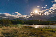 The quarter Moon shining over Maskinonge Pond at Waterton Lakes National Park, Alberta, on a very windy autumn night, with clouds moving in. <br /> <br /> This is a single 10-second exposure with the Nikon D750 at ISO 1600 and Sigma 24mm lens at f/2.8. The Moon creates a lens flare opposite its image.