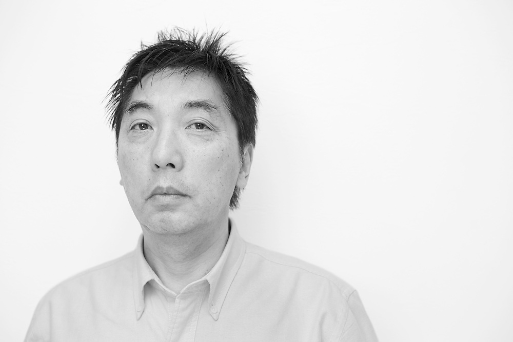 Black and white portrait photograph of sad Japanese middle age man
