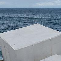 Cubes of concrete protect Puerto de Vega harbor in Asturias, Spain, against the Cantabrian sea.