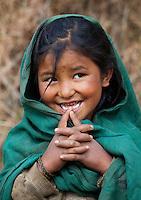 Portrait of a little Nepalese girl wearing a green shawl and smiling, Helambu Region, Nepal