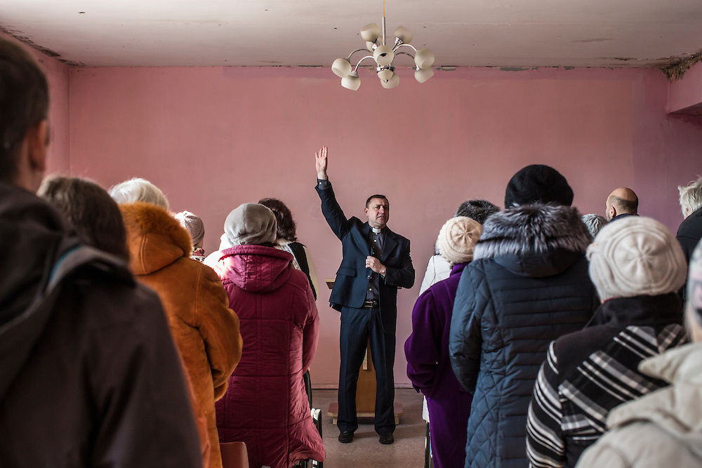 MARIINKA, UKRAINE - FEBRUARY 20, 2016:  Pastor Sergei Kosyak, center, leads a service at the Christian Help Center of the Church of the Transfiguration in Mariinka, Ukraine. The Donetsk suburb has been the scene of some of the heaviest fighting recently between Ukrainian forces and pro-Russian rebels. CREDIT: Brendan Hoffman for The New York Times