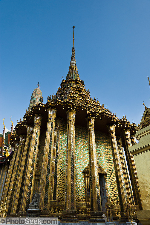 The Phra Mondop building is part of Wat Phra Kaew/Temple of the Emerald Buddha, at the Grand Palace, Bangkok, Thailand. King Rama I constructed the Phra Mondop building order to house the revised edition of the Buddhist Canon. The walls of the Phra Mondop are covered in green mirrored tiles inlaid with gold medallions depicting Buddha. The base of the walls are lined with two rows of small gilded guardian angels, each one slightly different. At the four corners of the Phra Mondop are stone Buddhas carved in the ninth century Javanese style. Sixteen twelve-cornered columns support the intricate multi-tier roof.