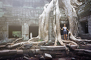 A woman explores the ancient temple grounds of Ta Prohm, Siem Reap, Cambodia