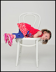 A 2 year old girl climbing on a chair.  Saturday July 7, 2012. Photo by Andrew Parsons/i-Images..All Rights Reserved ©Andrew Parsons/i-Images.See Instructions