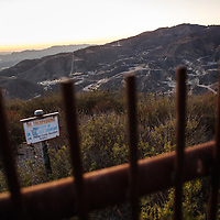 A No Trespassing sign and fence mark the boundary of the SoCalGas Aliso Canyon Storage Facility, looking towards where a leaking gas well and a relief well are being drilled, at the top of a public hiking trail from Bee Canyon Park as methane gas leaks from the SoCalGas Aliso Canyon Storage Facility well SS-25 in the Porter Ranch neighborhood of Los Angeles, California on Wednesday, December 30, 2015. The Aliso Canyon gas leak (also called Porter Ranch gas leak) was a massive natural gas leak that started on October 23, 2015. According to Wikipedia, an estimated 1,000,000 barrels per day was released from a well within the underground storage facility in the Santa Susana Mountains near Porter Ranch. The second-largest gas storage facility it belongs to the Southern California Gas Company (SoCalGas), a subsidiary of Sempra Energy. On Jan. 6, 2016, Governor Jerry Brown issued a State of Emergency. The Aliso gas leak carbon footprint is said to be larger than the Deepwater Horizon leak in the Gulf of Mexico. On Feb. 11, 2016 the gas company reported that it had the leak under control. On Feb. 18 state officials announced that the leak was permanently plugged. An estimated 97,100 tonnes of methane and 7,300 tonnes of ethane was released into the atmosphere, making it the worst natural gas leak in U.S. history in terms of its environmental impact. © 2015 Patrick T. Fallon