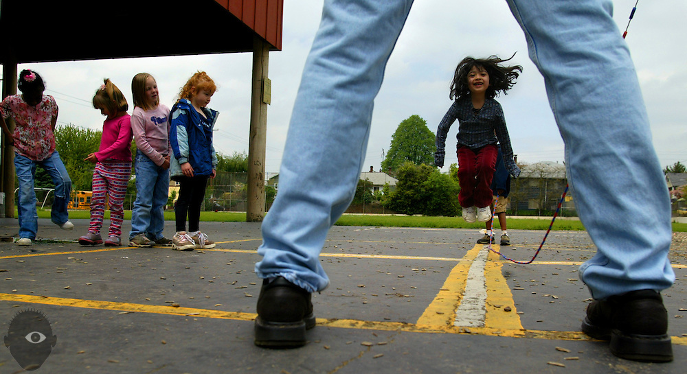 Anayanci DePaz (center), 6, catches some air as she enjoys some jump roping during recess at Grout Elementary School in Portland, Oregon. Kindergarten teacher Bob Parker (near) helps to keep the rope turning.