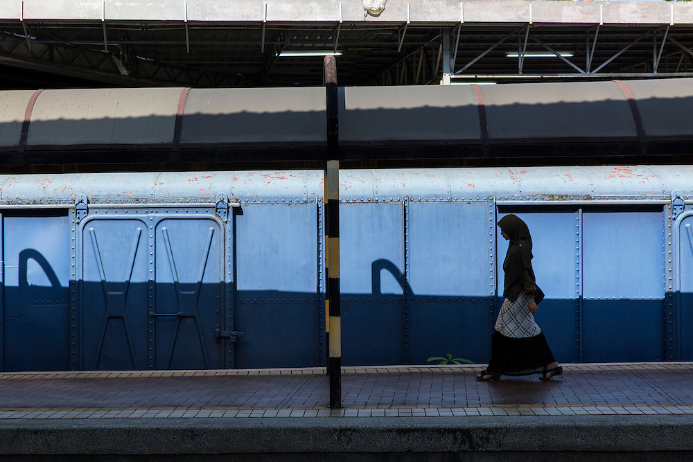 Asia, Malaysia, Kuala Lumpur, Young woman wearing head scarf walking on abandoned platform at train station