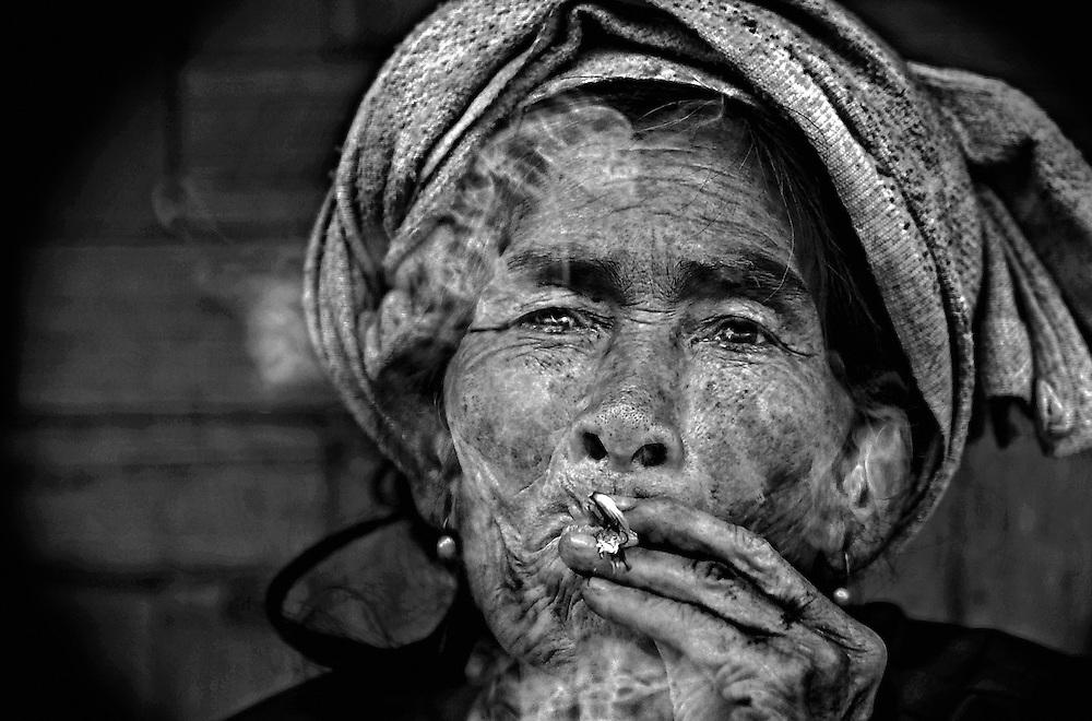 A Khamu woman taking time out for a smoke in the mountains near Luang Prabang, Laos.