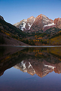 The Maroon Bells are reflected in Maroon Lake in Colorado on a still autumn morning. The Maroon Bells are a pair of mountains, the tallest of which is 14,156 feet (4,317 meters). The peaks are located in the Maroon Bells-Snowmass Wilderness of White River National Forest.