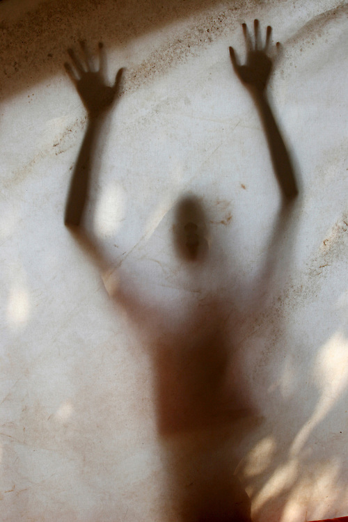 Shadow of a woman victim of rape behind a tent in Burundi Africa. @ Martine Perret. 24 October 2005