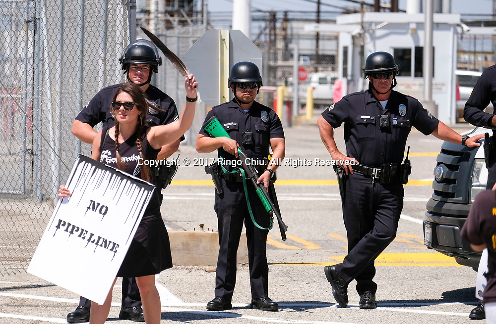 Police officers stand guard infant of the Tesoro Oil Refinery as thousands people participate in &quot;People's Climate March&quot; a climate change awareness march and rally, in Los Angeles, Saturday, April 29, 2017. The gathering was among many others of its kind held nationwide marking President Donald Trump's 100th day in office.(Photo by Ringo Chiu/PHOTOFORMULA.com)<br /> <br /> Usage Notes: This content is intended for editorial use only. For other uses, additional clearances may be required.