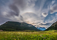 A partial lunar halo around the first quarter Moon over the flower-filled Blakiston Valley on a moody moonlit cloudy night at Waterton Lakes National Park, June 24, 2015. This is a 4-segment panorama with the Nikon D750 and 24mm lens, mounted portrait, and stitched with Photoshop and corrected with Wide Angle Adaptive Lens Correction to straighten the scene. Liberal use of Highlight and Shadow recovery in ACR and Shadows and Highlights in PS brought out the flower-filled foreground while retaining detail in the bright sky. Each segment was 30 seconds at f/2.8 and ISO 1600.