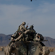 Marines on a Light Armored Vehicle prepare to go on patrol in and around Kandahar, Afghanistan as an AH1W Super Cobra helicopter flies by.