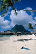 Bora Bora Lagoon Resort, Tahiti: snorkeling gear on beach, bungalows on lagoon; with Mount Pahia in the distance.