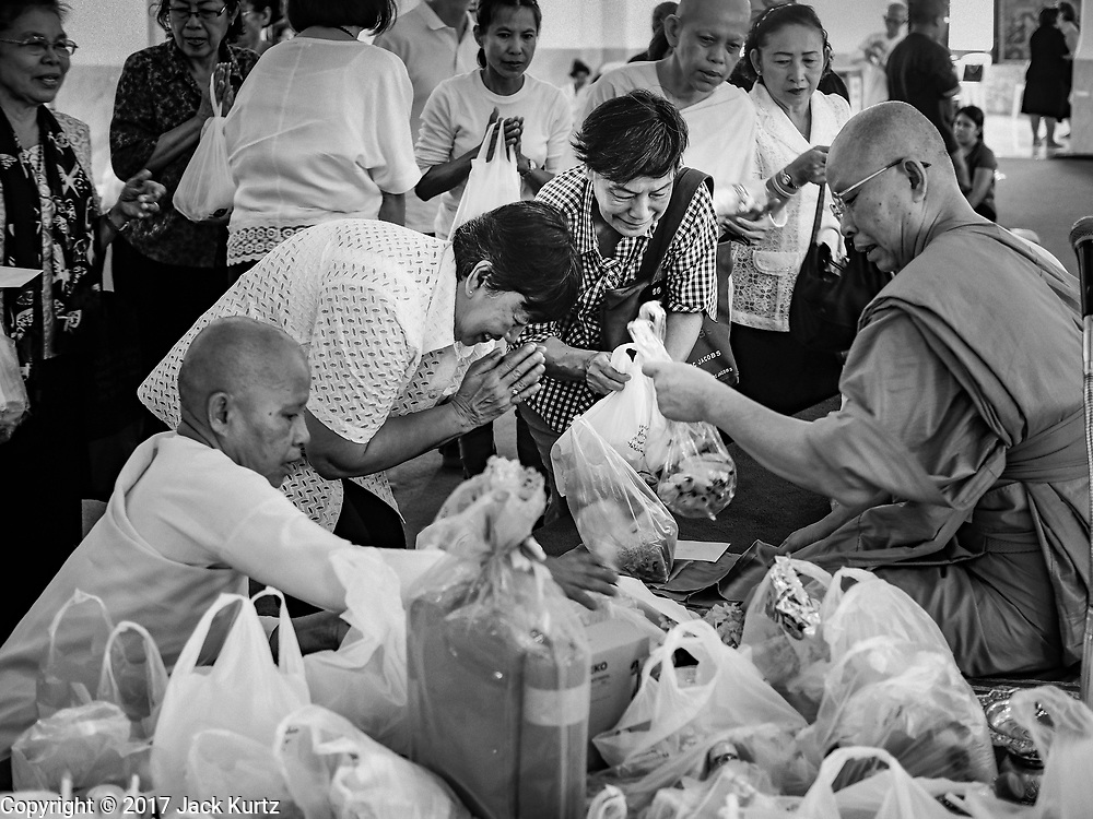 """11 APRIL 2017 - BANGKOK, THAILAND: A Buddhist monk accepts merit making offerings from people at Wat Chana Songkhram in Bangkok during a Songkran merit making service. Songkran is the traditional Thai Lunar New Year. It is celebrated, under different names, in Thailand, Myanmar, Laos, Cambodia and some parts of Vietnam and China. In most places the holiday is marked by water throwing and water fights and it is sometimes called the """"water festival."""" This year's Songkran celebration in Thailand will be more subdued than usual because Thais are still mourning the October 2016 death of their revered Late King, Bhumibol Adulyadej. Songkran is officially a three day holiday, April 13-15, but is frequently celebrated for a full week. Thais start traveling back to their home provinces over the weekend; busses and trains going out of town have been packed.     PHOTO BY JACK KURTZ"""