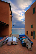 """A small square in the town of Varigotti in Liguria, Italy, an amazing village with the houses built directly at the beach. This scene resembles to me as a """"behind the curtains"""" view, with the houses being the curtains and the boats being the actors ready to enter the ocean scene and play their role."""