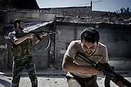 SYRIA, ALEPPO. A Syrian rebel fires toward regime forces as his comrade ducks, in the Old City of Aleppo on September 24, 2012 ALESSIO ROMENZI