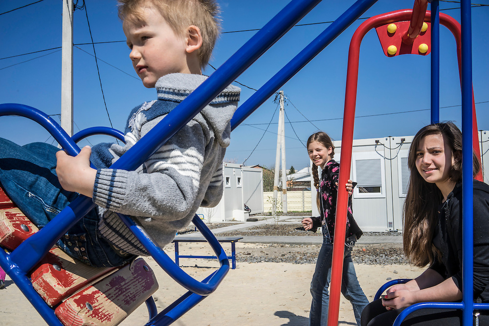 Young residents of a cluster of prefabricated container houses known as Transit City play on a swingset on Monday, April 27, 2015 in Kharkiv, Ukraine. The spot is home to 83 families, and 387 people total, who are IDPs forced to flee eastern Ukraine because of fighting between Ukrainian forces and pro-Russian rebels. CREDIT: Brendan Hoffman/Prime for the Wall Street Journal UKRMIGRATION