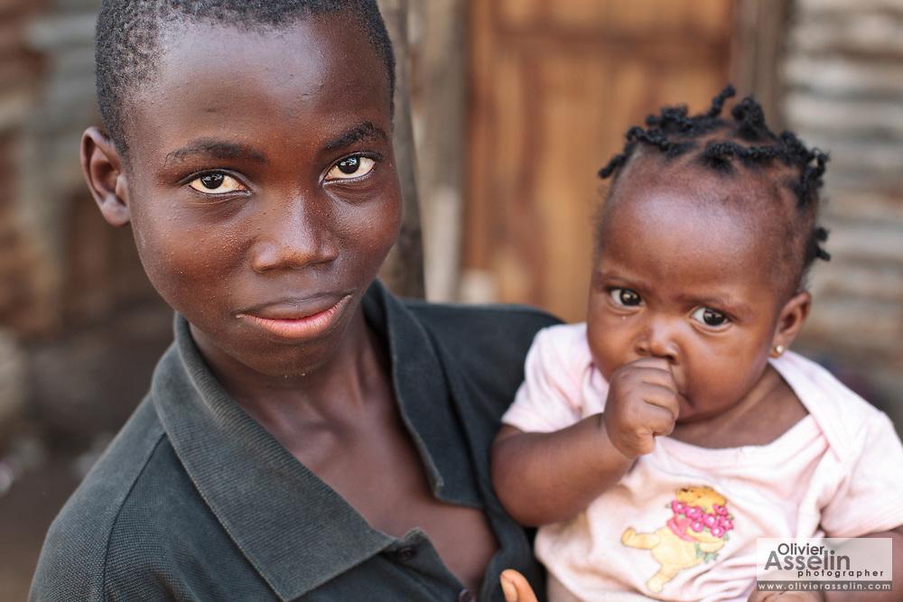A boy holds a young girl in his arms in the Clara town slum in Monrovia, Montserrado county, Liberia on Thursday April 5, 2012.