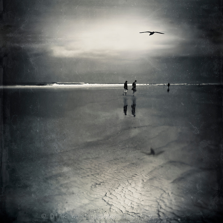 Couple taking a stroll on a beach at low tide. Manipulated and tinted photograph.<br />