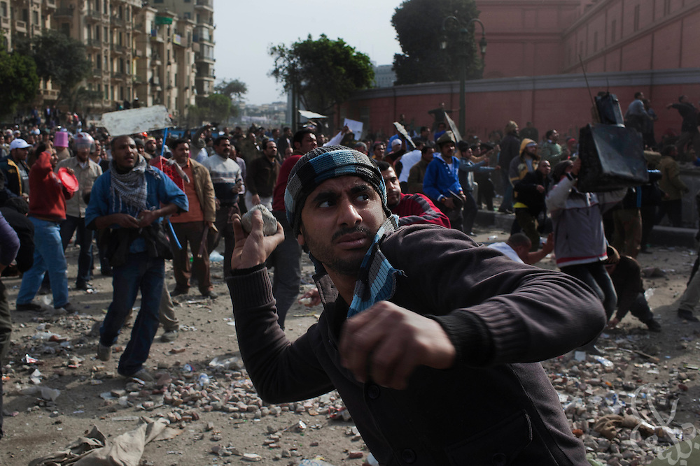 Anti-Hosni Mubarak protesters throw rocks and bricks at nearby Mubarak supporters as they defend the Tahrir square area February 03, 2011 where they have remained for a week following massive and unprecedented demonstrations. (Photo by Scott Nelson)