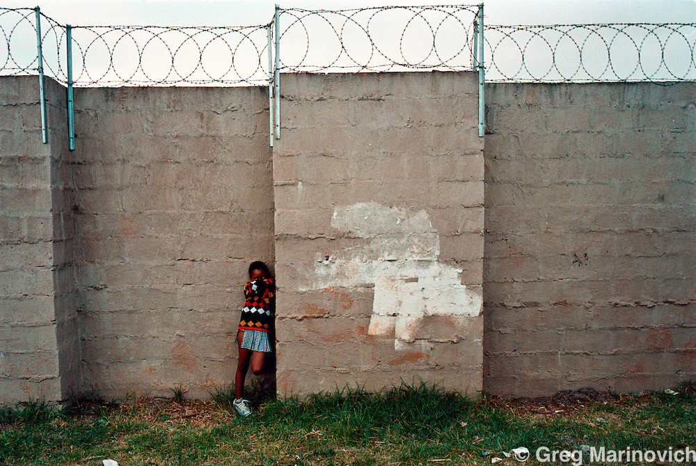 IPMG0128 South Africa, Edendale 2000: .A young girl nervously waits to take her virginity test in a sport stadium in Edendale, KwaZulu Natal, South Africa, Aug 2000. People are desperate to find community solutiions to the pandemic. The myth that sleeping with a virgin will rid a sufferer of the disease means the tests - meant to promote abstenance - also make the girls targets. Southern Africa has the highest per capita Aids sufferers, and KwaZulu Natal is the worst hit province. ..Photograph by Greg Marinovich