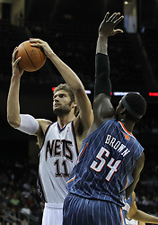 Apr 11; Newark, NJ, USA; New Jersey Nets center Brook Lopez (11) hits a shot over Charlotte Bobcats center Kwame Brown (54) during the first half at the Prudential Center.