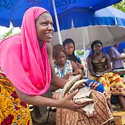 LÉGENDE: Rosine souriante et marchande ses poissons à un client. LIEU: Marché de Chagoua, N'Djaména, Tchad. PERSONNE(S): Rosine Remadsi (à Gauche) légèrement coubrée, sourit. Tient entre ses mains les poissons qu'elle vend. En arrière plan, d'autres vendeuses assisent devant leurs stands au marché de Chagoua.