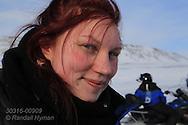 Woman takes break during snowmobile trip in April between Longyearbyen and Barentsburg; Svalbard, Norway.