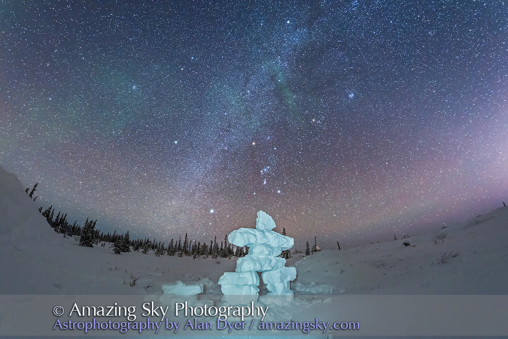 Orion and the winter stars and Milky Way over a mock-up inukshuk figure made of snow blocks, at the Churchill Northern Studies Centre, Manitoba. The human figure of the inukshuk mirrors the figure of Orion in the sky. This is a single expsoure with the 12mm full frame Rokinon fish-eye lens and Nikon D750. The inukshuk is painted with a white LDE headlamp.